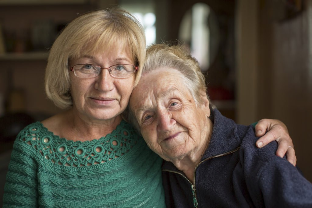 elderly lady and slightly younger lady looking at camera