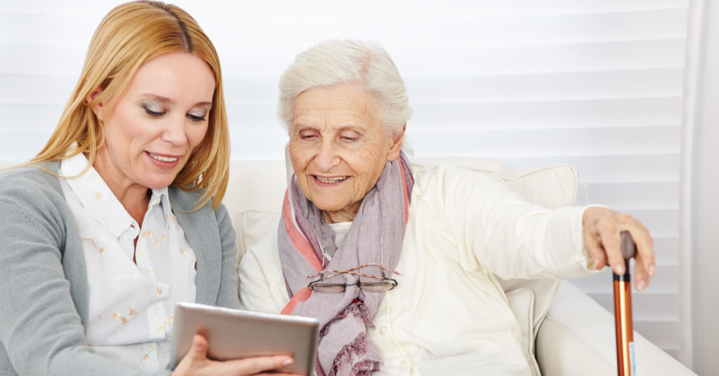 A carer using a tablet computer with an elderly woman