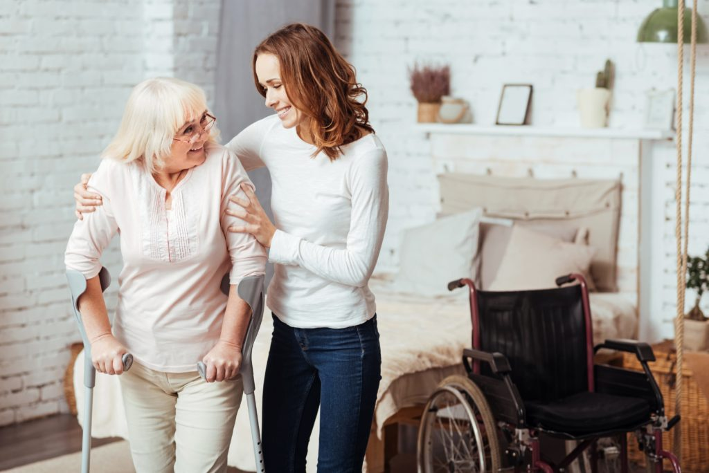 an elderly lady walking with the help of a female carer
