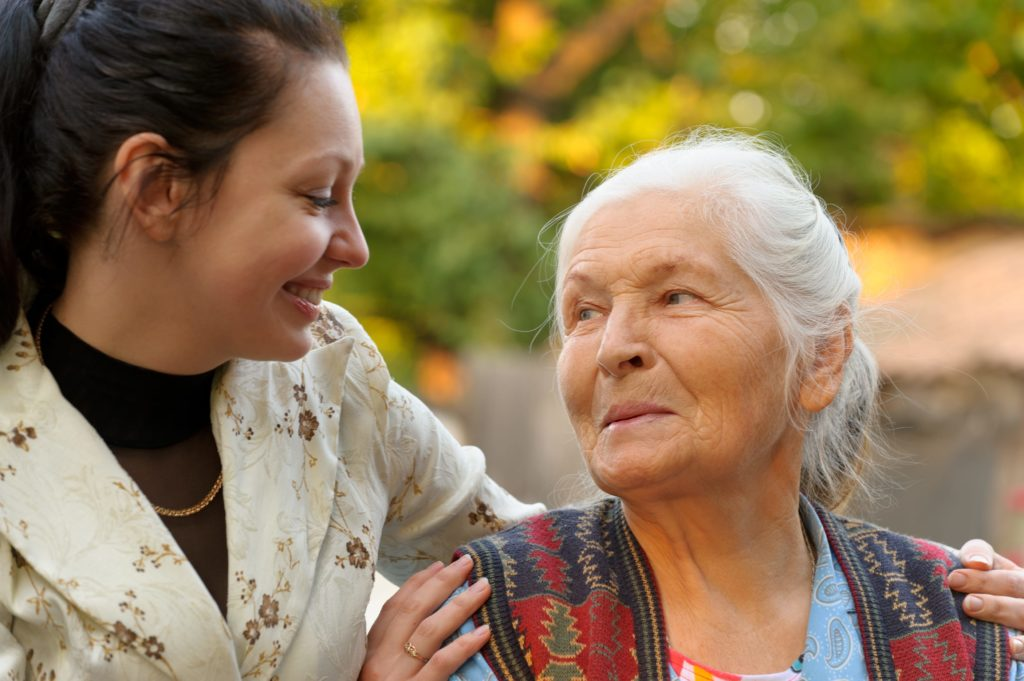 elderly lady looking up at a younger woman