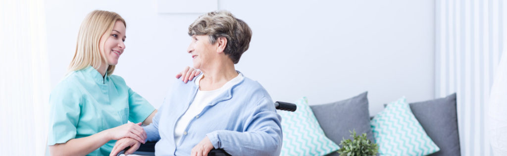 Carer and elderly lady smiling at one another