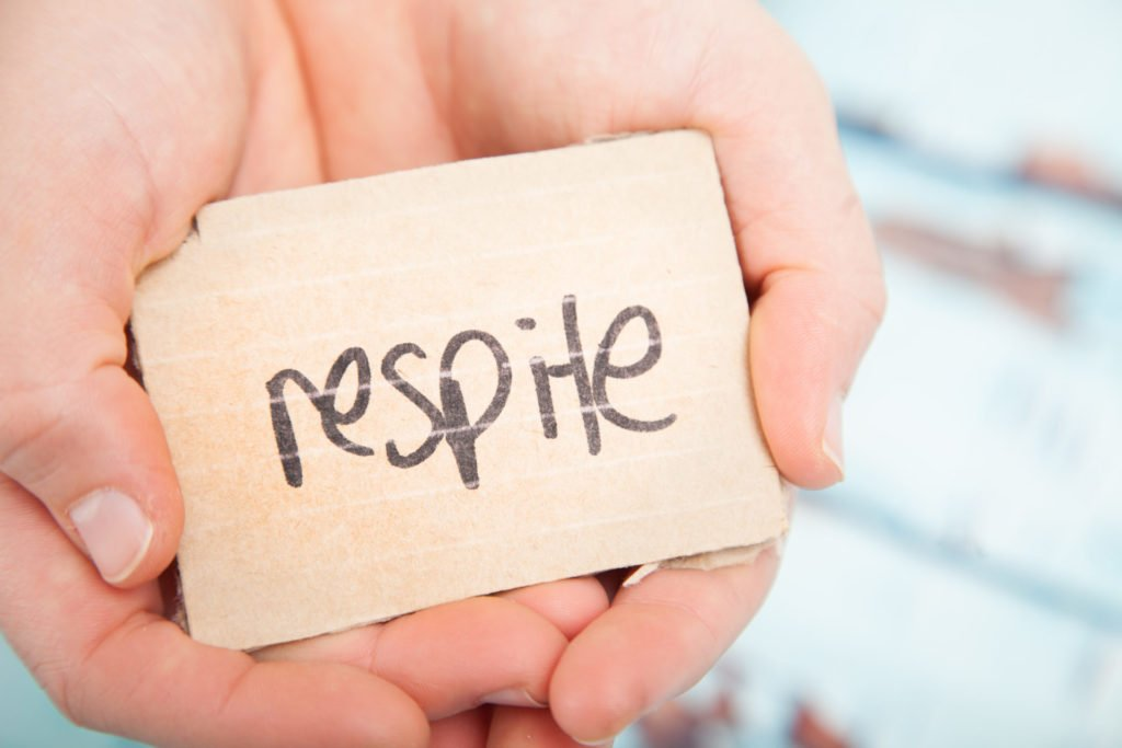 Respite written on a block, being held in two hands