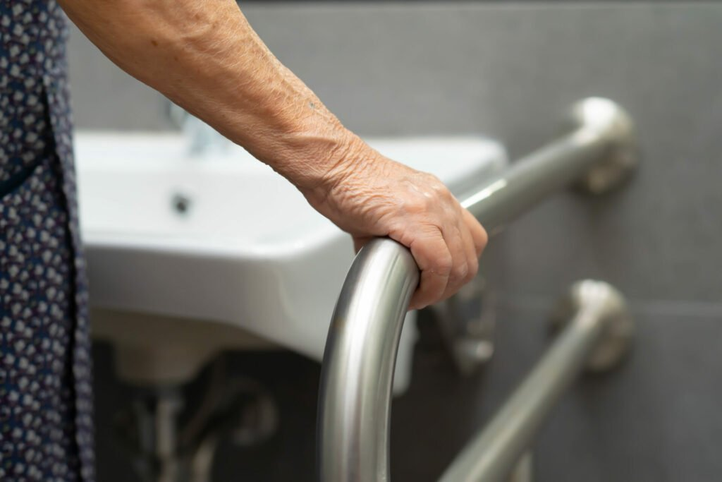 Elderly lady using a grab rail to stand at the sink